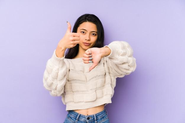 親指を上に、親指を下に示す紫色の壁に孤立した若い女性