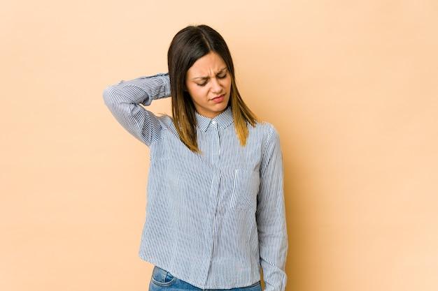 座りがちな生活のために首の痛みに苦しんでいるベージュの背景に孤立した若い女性。