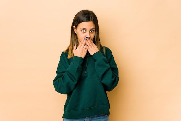 心配そうに見えて手で口を覆っているベージュの壁に分離された若い女性。
