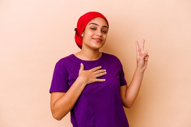 誓いを立てて、胸に手を置いて、ベージュの壁に孤立した若い女性