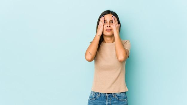 若い女性が楽しんで青い背景に分離された手のひらで顔の半分をカバーします。