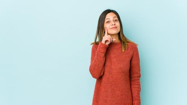 指でナンバーワンを示す青い背景で隔離の若い女性。