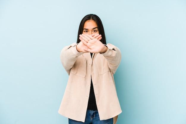Молодая женщина изолирована на синем, делая жест отрицания