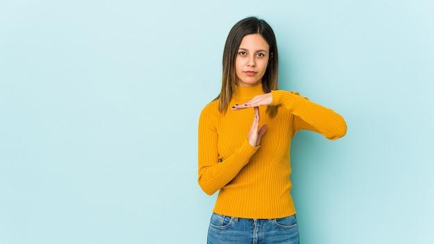Молодая женщина, изолированные на синем, показывая жест тайм-аута.