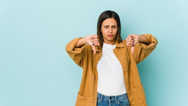 Молодая женщина изолирована на синем, показывая большой палец вниз и выражая неприязнь.