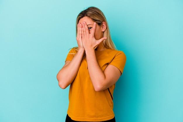 Молодая женщина, изолированная на синей стене, моргает сквозь пальцы испуганно и нервно