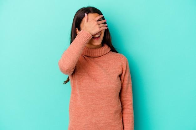 Молодая женщина, изолированная на синей стене, закрывает глаза руками, широко улыбается в ожидании сюрприза