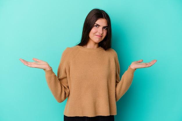 Молодая женщина изолирована на синей стене, сомневаясь и пожимая плечами в вопросительном жесте