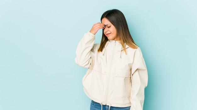 Молодая женщина изолирована на синей стене с головной болью, касаясь передней части лица.