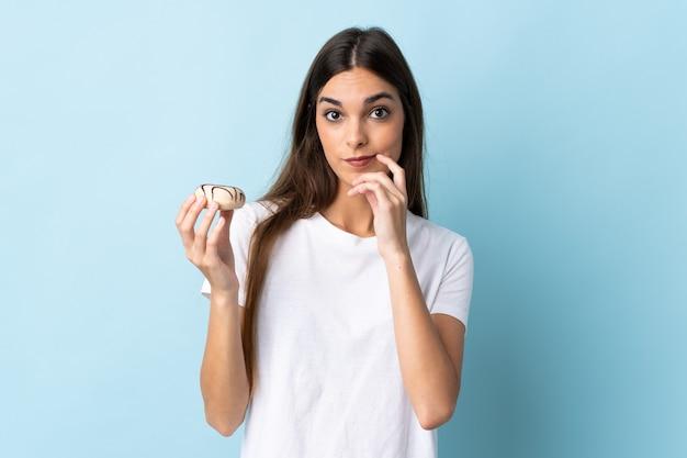 ドーナツを保持している青い壁に分離された若い女性