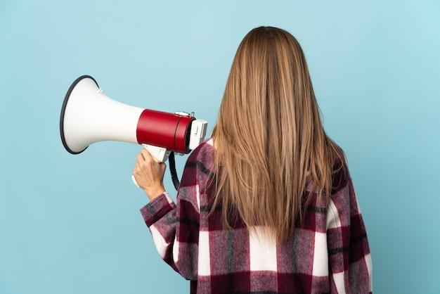 Молодая женщина, изолированные на синей стене, держа мегафон и в задней позиции