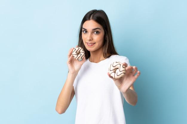 幸せな表情でドーナツを保持している青い壁に分離された若い女性
