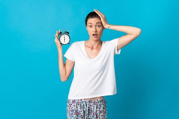 잠옷에 파란색 벽에 고립 된 젊은 여자와 놀란 표정으로 시계를 들고