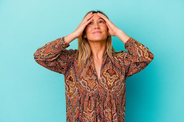 Молодая женщина, изолированная на синей стене, радостно смеется, держась за голову