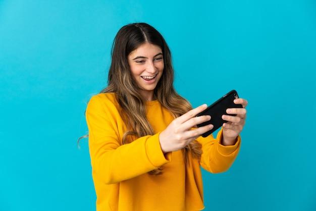 Молодая женщина изолирована на синей стене, играя с мобильным телефоном