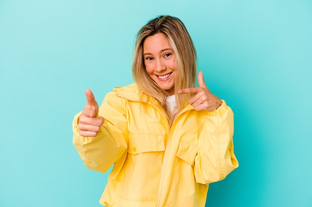 손가락으로 앞을 가리키는 파란색 벽에 고립 된 젊은 여자