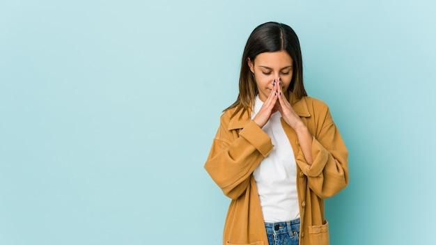 Молодая женщина изолирована на синей стене молится, показывая преданность, религиозный человек ищет божественного вдохновения.