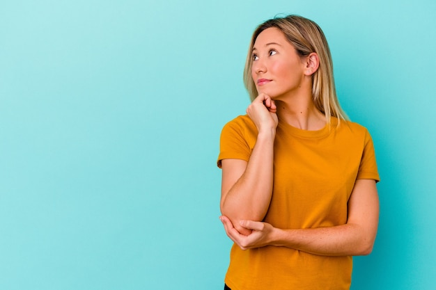 Молодая женщина, изолированная на синей стене, расслабилась, думая о чем-то, глядя на копию пространства