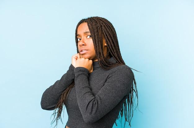 Молодая женщина, изолированная на синей стене, испугалась и испугалась