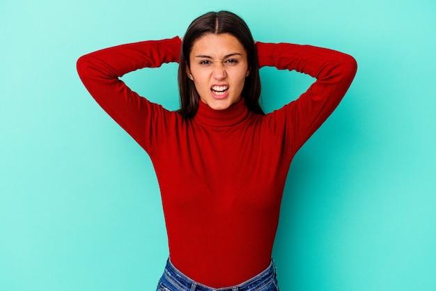 怒りで叫んで青い壁に孤立した若い女性