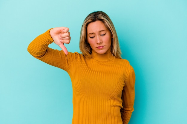 Молодая женщина изолирована на синей стене, показывая жест неприязни, пальцы вниз концепция несогласия