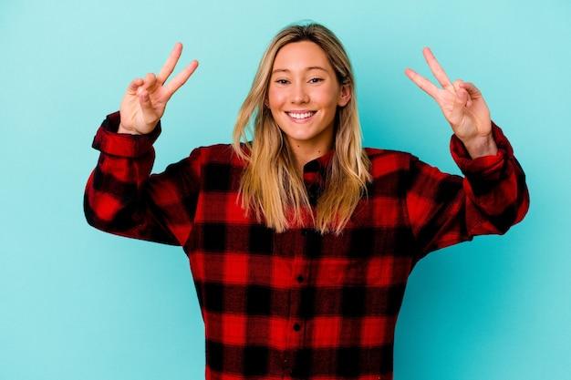 승리 기호를 표시 하 고 광범위 하 게 웃 고 파란색 벽에 고립 된 젊은 여자