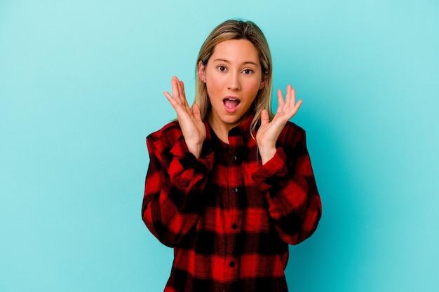 Молодая женщина изолирована на синей стене удивлена и шокирована
