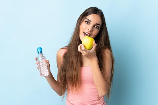 물 한 병으로 파란색 벽에 격리하고 사과를 먹는 젊은 여자