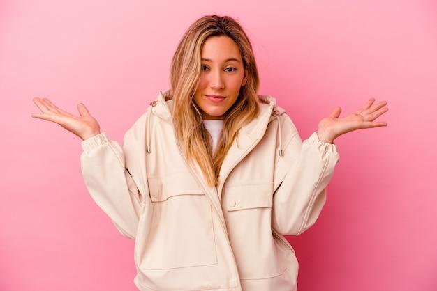 Молодая женщина, изолированная на розовой стене, смущенная и сомневающаяся, пожимая плечами, чтобы держать копию пространства