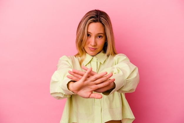 거부 제스처를 하 고 분홍색 벽에 고립 된 젊은 여자