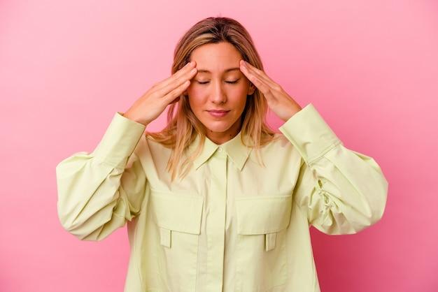 顔の正面に触れて、頭痛を持っているピンクの壁に孤立した若い女性