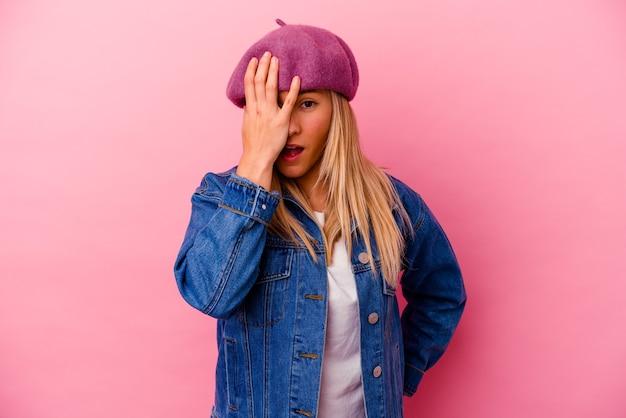 手のひらで顔の半分を覆うことを楽しんでピンクの壁に分離された若い女性
