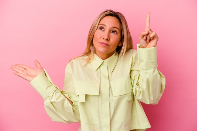 핑크 벽 잡고 손에 제품을 보여주는에 고립 된 젊은 여자