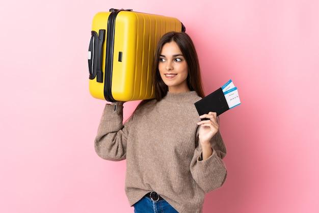 Молодая женщина изолирована на розовой стене в отпуске с чемоданом и паспортом