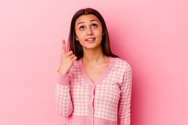 분홍색 벽에 고립 된 젊은 여자는 빈 공간을 보여주는 두 앞 손가락으로 나타냅니다