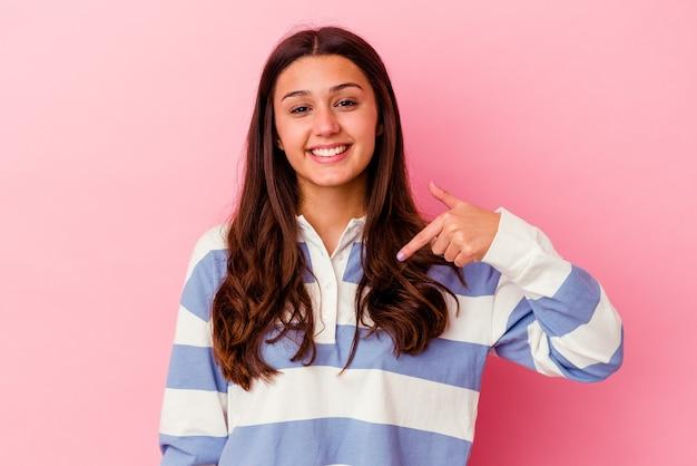 シャツのコピースペースを手で指しているピンクの壁の人に孤立した若い女性、誇りと自信を持って