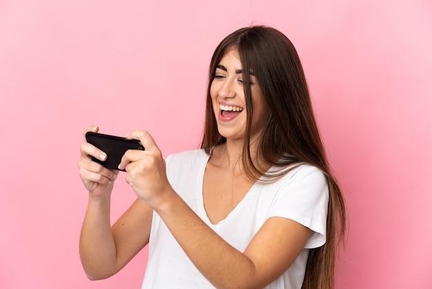 Молодая женщина изолирована на розовой стене, играя с мобильным телефоном