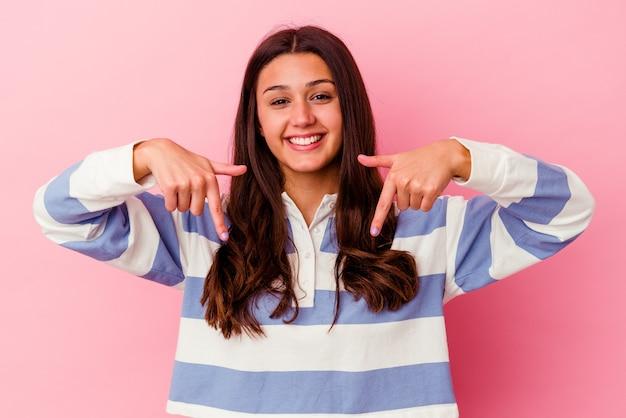 분홍색 벽에 고립 된 젊은 여자는 손가락, 긍정적 인 느낌으로 아래를 가리 킵니다.