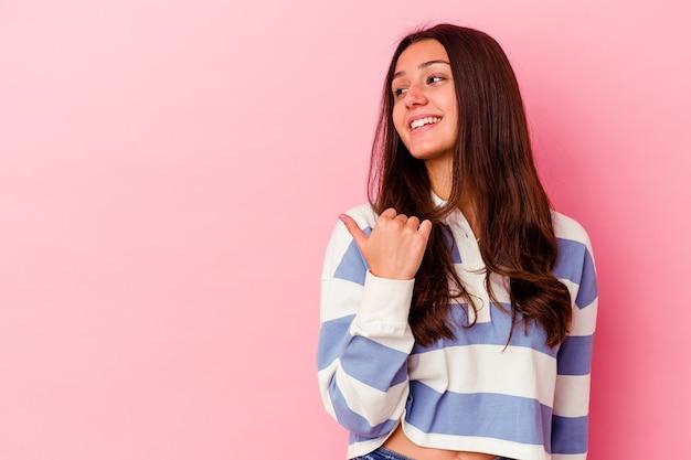 親指の指を離れて、笑ってのんきなピンクの壁のポイントで隔離の若い女性