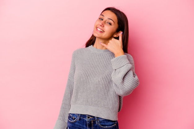指で携帯電話の呼び出しジェスチャーを示すピンクの壁に分離された若い女性