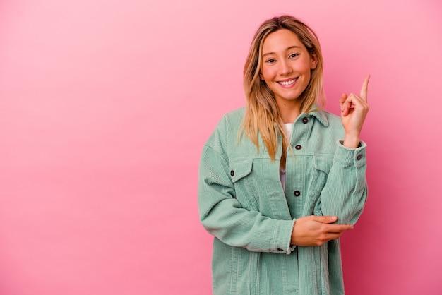 Молодая женщина изолирована на розовой стене, показывая пальцем номер один