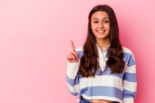 指でナンバーワンを示すピンクの壁に分離された若い女性
