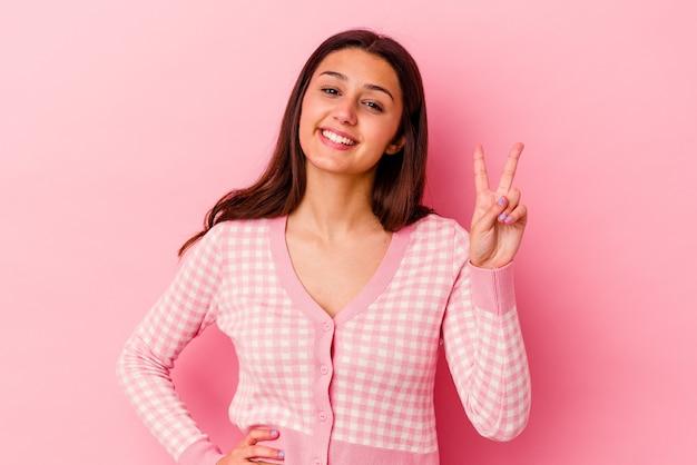 ピンクの壁に分離された若い女性