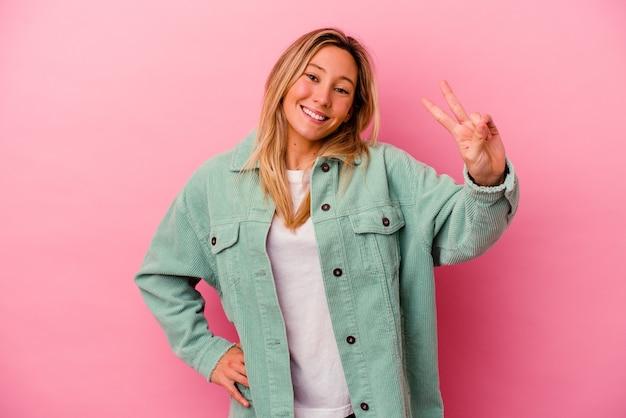 Молодая женщина изолирована на розовой стене, показывая знак победы и широко улыбаясь
