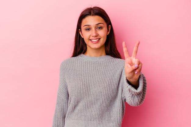 勝利のサインを示し、広く笑顔のピンクの壁に孤立した若い女性