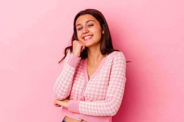 행복하고 자신감이 웃는 분홍색 벽에 고립 된 젊은 여자, 손으로 턱을 만지고