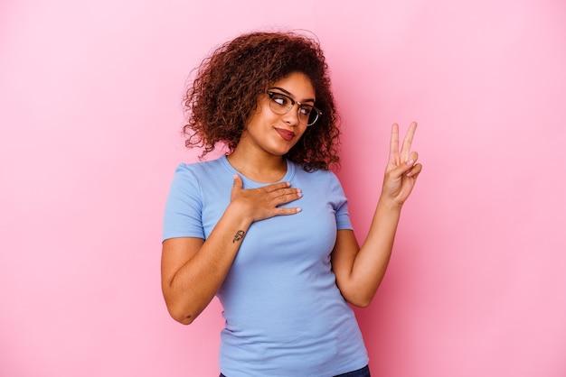 誓いを立てて、胸に手を置いて、ピンクの壁に孤立した若い女性