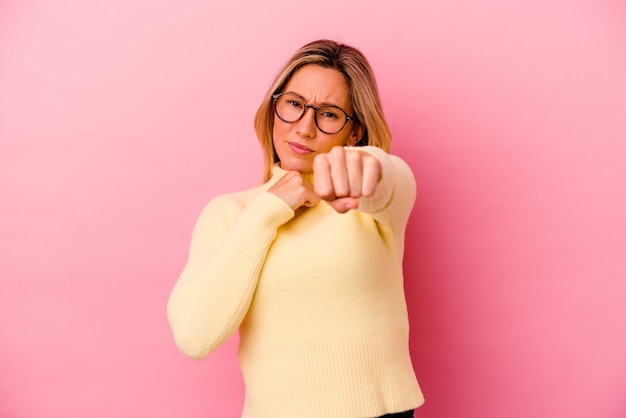 Молодая женщина изолирована на розовой стене, бросает удар, гнев, борьба из-за спора, бокс