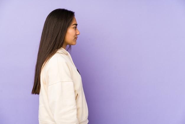 紫の視線左、横向きのポーズで孤立した若い女性。