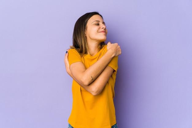 Молодая женщина изолирована на фиолетовых объятиях, беззаботно улыбается и счастлива.